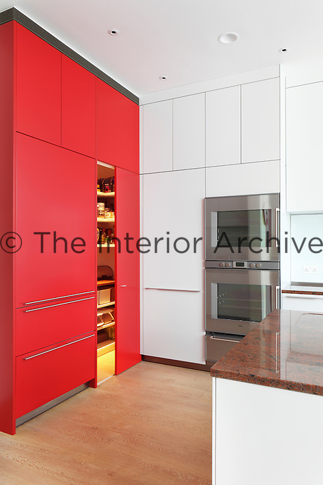 A sliding door within a red storage unit reveals a pantry in this modern Bulthaup kitchen
