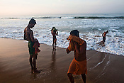 Tourists seen drying themselves to the beach after taking an early morning bath in Bay of Bengal in Puri, Orissa, India. A dip in its salty waters is believed to hold great religious significance, as a result these golden sand beaches sees is a never-ending rush of pilgrims and tourists. Photo: Sanjit Das/Panos