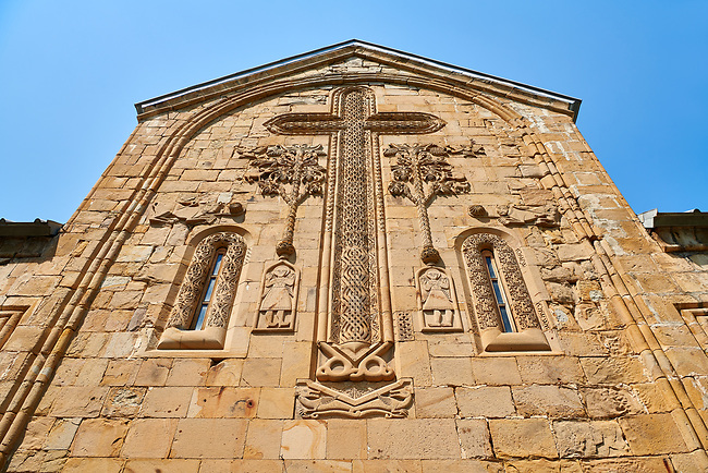 Pictures & images of the Church of the Assumption exterior bas relief Georgian stone work of a crucifix and angel figures,1689, Ananuri castle complex & Georgian Orthodox churches, 17th century, Georgia (country).<br /> <br /> Ananuri castle is situated next to the Military Road overlooking the Aragvi River in Georgia, about 45 miles (72 kilometres) from Tbilisi. It was the castle of the eristavis (Dukes) of Aragvi from the 13th century and was the scene of numerous battles. In 2007 Ananuri castle was enscribed on the   UNESCO World Heritage Site tentative list.<br /> <br /> The exterior of The Church of the Assumption is highly decorated with Georgian bas relief sculpture. Above the main door is a geometric stone relief of a crucifix which is the whole height of the facade. Either side of the crucifix are reliefs of the tree of life below which are reliefs of naive style angels.
