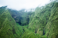 An aerial view of a large verdant canyon with waterfalls on Kaua'i.