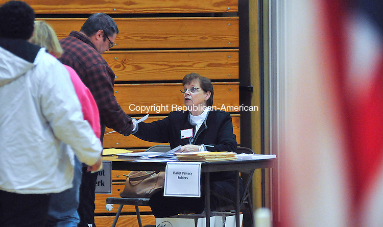 WINSTED, CT-06 NOVEMBER 2012--110612JS05- Ballot Clerk Milly Hudak hands ballots to votersTuesday at Pearson Middle School in Winsted. According to officials, there was a steady stream of voters throughout the morning. .Jim Shannon Republican-American