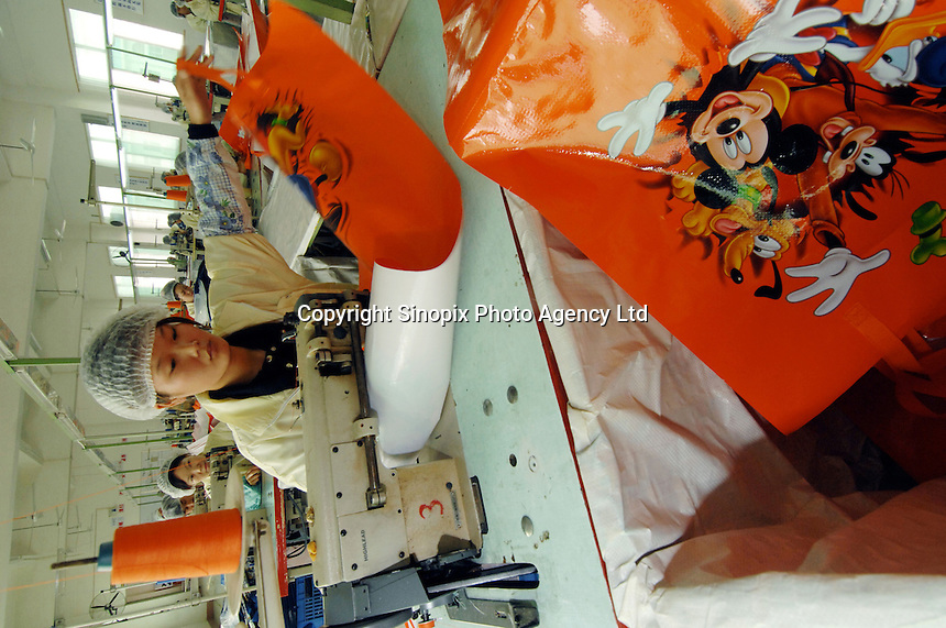 Workers make Disney woven plastic carrier bags at the Richall factory in Donguan, Guangdong province, China. The woven plastic bags can be used many times and are seen as environmentally friendly. The company makes plastic bags for several clients including Disney and Sainsbury's..