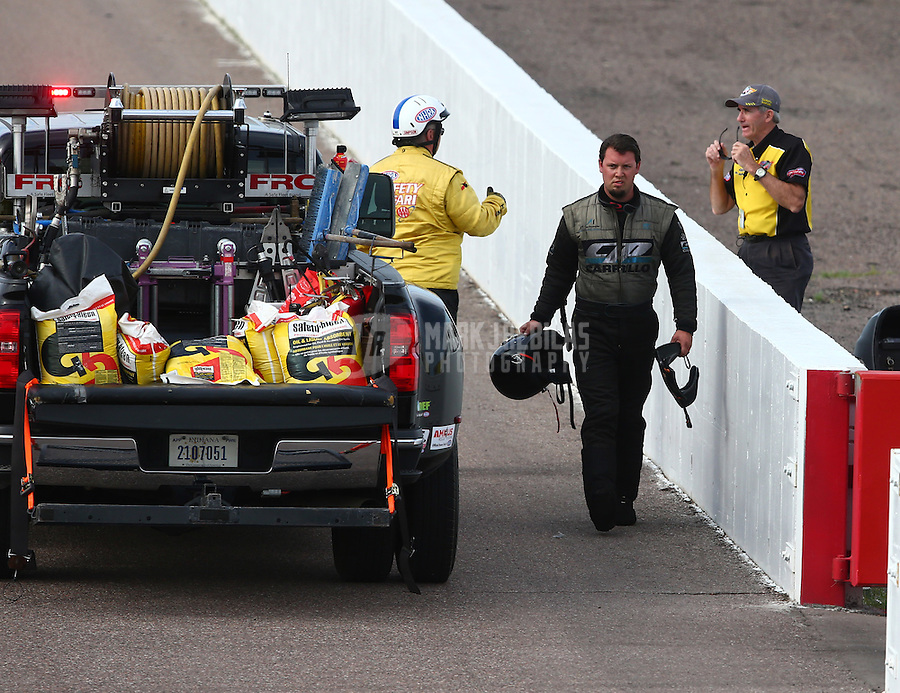 Feb 21, 2015; Chandler, AZ, USA; NHRA funny car driver Shane Westerfield walks along the guardwall after experiencing a fire during qualifying for the Carquest Nationals at Wild Horse Pass Motorsports Park. Mandatory Credit: Mark J. Rebilas-