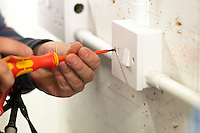 Student electrician puts the cover on a domestic switch, Able Skills, Dartford, Kent.