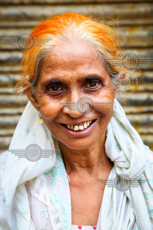 A woman with dyed hair.<br /> <br /> It is very common in Bangladesh to see older people with dyed orange hair, men with orange beards or orange moustaches and women with orange hair. The dye used is from the flowering Henna plant. The practice comes from the widely held belief that the Prophet Muhammad dyed his beard and hair. It is also common among people returning from Hajj. Some Muslims believe that henna is the only dye they are free to use for colouring their hair.