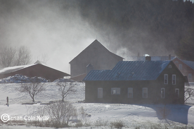 Snow blowing off metal roofs on a frigid January day in Waitsfield, VT, USA