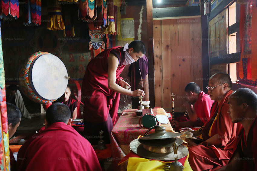 Buddhist monks performing rituals and prayers in temple. A traditional Puja celebration, a yearly Buddhist festival by the local community, Chuchizshey temple, Bumthang, Bhutan..Bhutan the country that prides itself on the development of 'Gross National Happiness' rather than GNP. This attitude pervades education, government, proclamations by royalty and politicians alike, and in the daily life of Bhutanese people. Strong adherence and respect for a royal family and Buddhism, mean the people generally follow what they are told and taught. There are of course contradictions between the modern and tradional world more often seen in urban rather than rural contexts. Phallic images of huge penises adorn the traditional homes, surrounded by animal spirits; Gross National Penis. Slow development, and fending off the modern world, television only introduced ten years ago, the lack of intrusive tourism, as tourists need to pay a daily minimum entry of $250, ecotourism for the rich, leaves a relatively unworldly populace, but with very high literacy, good health service and payments to peasants to not kill wild animals, or misuse forest, enables sustainable development and protects the country's natural heritage. Whilst various hydro-electric schemes, cash crops including apples, pull in import revenue, and Bhutan is helped with aid from the international community. Its population is only a meagre 700,000. Indian and Nepalese workers carry out the menial road and construction work.