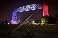 An anchor in Canal Park is framed by the patriotically-lit Aerial Lift Bridge for the Independence Day celebrations.<br /> <br /> The Aerial Lift Bridge is one of the most-recognized iconic landmarks of Duluth. In a mere 55 seconds, the bridge rises to 138 feet, making it the quickest and biggest lift bridge in the world.