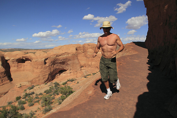 Man descending hiking trail in Arches National Park, Moab, Utah, USA. .  John offers private photo tours in Arches National Park and throughout Utah and Colorado. Year-round.