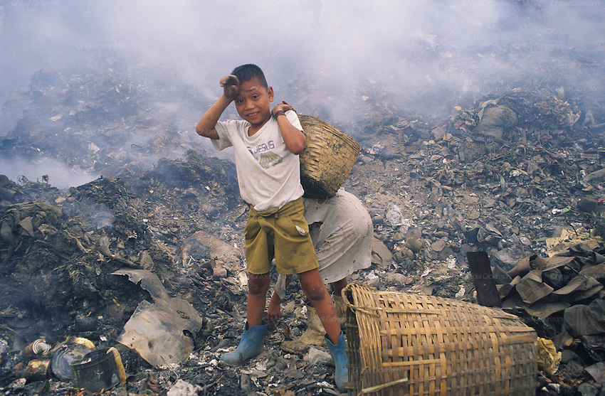 Asia, Philippines, Manilla, Smokey Mountain Rubbish dump. Child with 'Jesus' shirt. Thousands of poor and often indigenous people work sifting through the rubbish, recycling materials such as paper, various metal and plastic. They earn about $1 a day. The place is rife with disease.Photograph © Nigel Dickinson