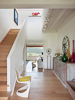 The entrance hall is light and airy and decorated in neutral tones. A view through to the sitting room beyond gives a sense of space.