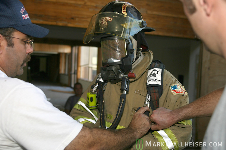 With his eyes covered inside his mask, one of the firefighters gets assistance from battalion chief Wes Roberts, left, and another firefighter prior to his turn in the Tallahassee Fire Department's safety and survival training to teach firefighters how to find their way out of a commercial building fire alive when it's to smoky to see and they are running out of air in their tanks  June 8, 2007.  The training was conducted at the old Professional Development building that is scheduled for demolition next week.    (Mark Wallheiser/TallahasseeStock.com)