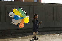 Boy selling balloons.