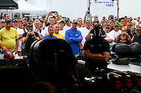 Oct 6, 2013; Mohnton, PA, USA; Spectators look on as NHRA funny car driver Alexis DeJoria warms up her car in the pits during the Auto Plus Nationals at Maple Grove Raceway. Mandatory Credit: Mark J. Rebilas-