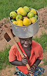 A woman carries mangoes in Mvula, Malawi...