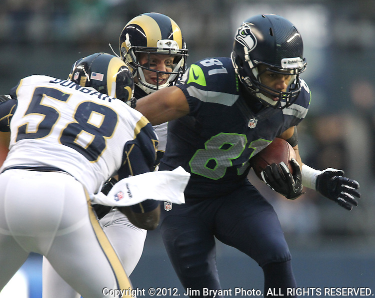 Seattle Seahawks Golden Tate is dragged down from behind by St. Louis Rams safety Craig Dahl and linebacker Jo-Lonn DUnbar after catching an 18-yard pass from quarterback Russell Wilson at CenturyLink Field in Seattle, Washington on December 30, 2012.   Tate caught four passes for 105 yards in the Seahawks 20-13 come from behind win over the Rams.    © 2012. Jim Bryant Photo. All Rights Reserved.