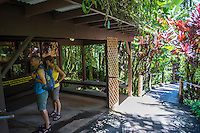 Two tourists read a sign and look at photos of the founders of the Hawaii Tropical Botanical Garden, Papa'ikou, Big Island of Hawaiʻi.