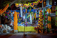 A man sits next to a market stall is decked out in colourful flowers on the occasion of Diwali, one of the biggest festival for Hindus.