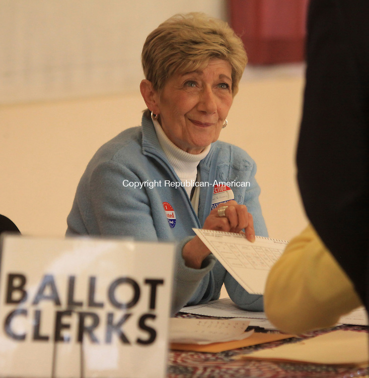 LITCHFIELD, CT - 5 November 2013 - 110513JM05 - Barbara Williams, a ballot clerk in Litchfield, hands a ballot to a voter at the Litchfield firehouse polling place on Tuesday. John McKenna Photo