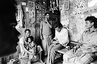 India. Province of Gujarat. Alang. Workers, all men, enjoy a day rest on the sunday. They seat on a bench, listen to music and talk together on the doorstep of their wood house. A father holds his son in his arms. Alang, located in the Gulf of Khambhat, is a ships breaking place and is considered as the biggest scrapyard in the world. © 1992 Didier Ruef