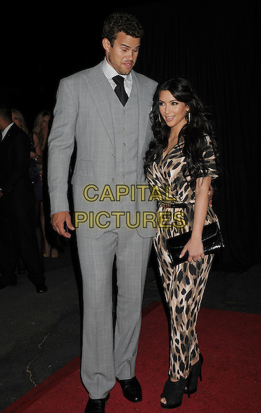 Kris Humphries and Kim Kardashian.The Launch Party for The Kardashian Kollection for Sears held at The Colony in Hollywood, California, USA..August 17th, 2011.full length black brown beige leopard print jumpsuit clutch bag belt grey gray suit waistcoat tall short couple eyes closed funny face clutch bag.CAP/ROT/TM.©Tony Michaels/Roth Stock/Capital Pictures