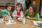 Children making a ginger bread house with mom's help