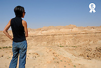 Tunisia, North Tozeur, woman looking at landscape, rear view (Licence this image exclusively with Getty: http://www.gettyimages.com/detail/sb10065474cw-001 )