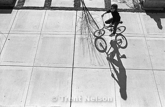 Kid riding bike and his shadow at Utah Valley Community College.<br />