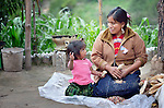 Jovita Guzman, a Maya Mam woman, pulls the grain off of corn at her home in Comitancillo, Guatemala, with help from her two-year old daughter Marilisa.
