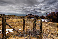 Cornerposts of a fence line with Cerro Cuate in the background in the Rio Puerco Valley of noethwestern New Mexico.