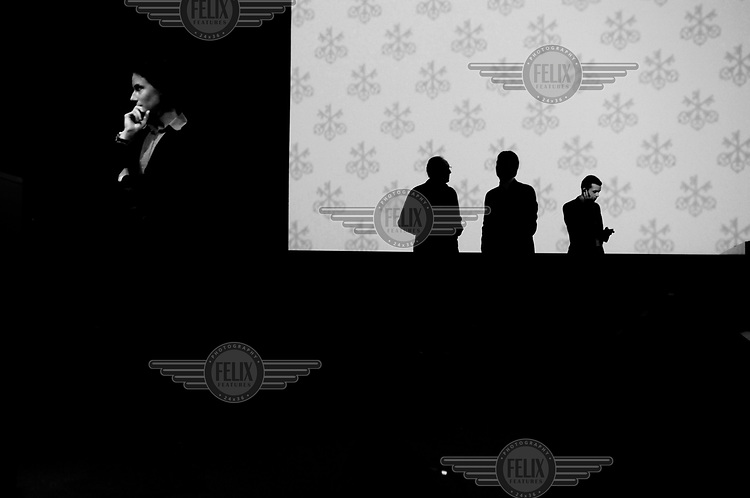A female security guard at the UBS annual shareholder's meeting (AGM). In the background senior staff are silhouetted against a projection of the bank's triple key logo. /Felix Features