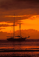 LA VIOLANTE, a 1920s DOUBLE-MASTED SCHOONER, and ORANGE SUNSET with CLOUD COVER over PACIFIC OCEAN - YASAWA ISLANDS, FIJI