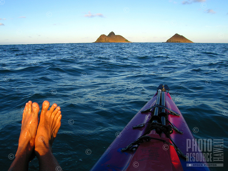 A man's feet next to the front of a kayak with secured paddles floating towards the Mokulua Islands, Windward O'ahu.