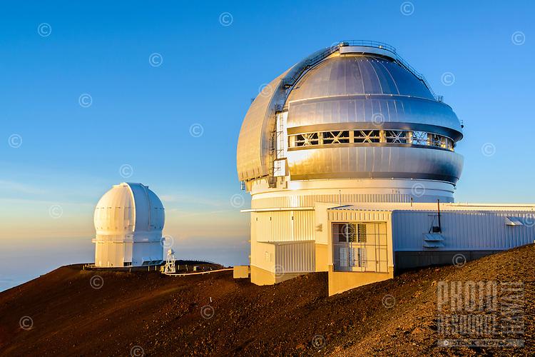 Two observatories reflect the setting sun at the summit of Mauna Kea, Island of Hawai'i.