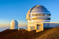Two observatories reflect the setting sun at the summit of Mauna Kea, Island of Hawai'i.