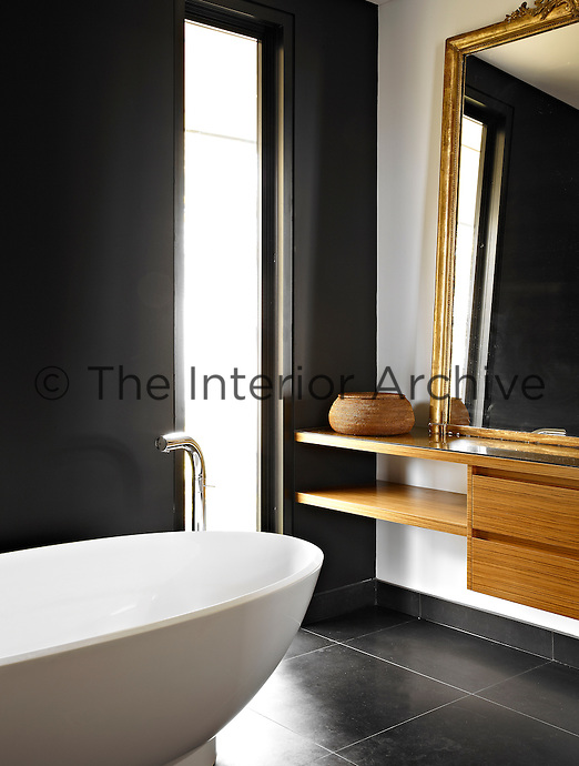 The contemporary bathroom echoes the design of the rest of the property and features black walls and a black basalt stone floor