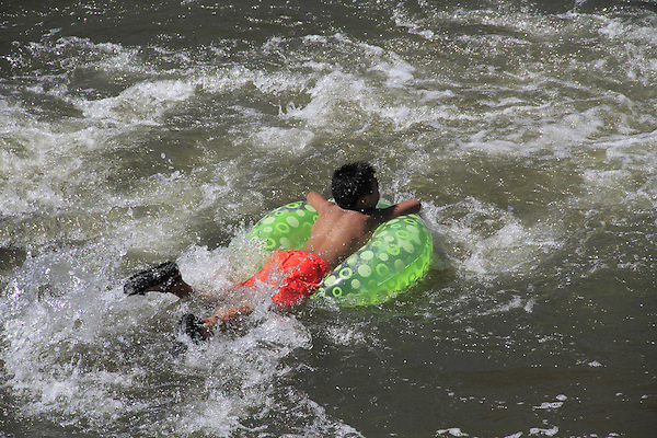 Boy floating river in inner tube at Boulder Creek, Boulder, Colorado. .  John offers private photo tours in Denver, Boulder and throughout Colorado. Year-round.