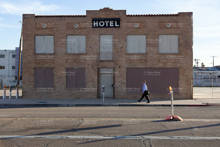 USA. Arizona state. Phoenix. Downtown. A business man walks on a sidewalk and passes in front of a deserted hotel. 27.01.2016 © 2016 Didier Ruef