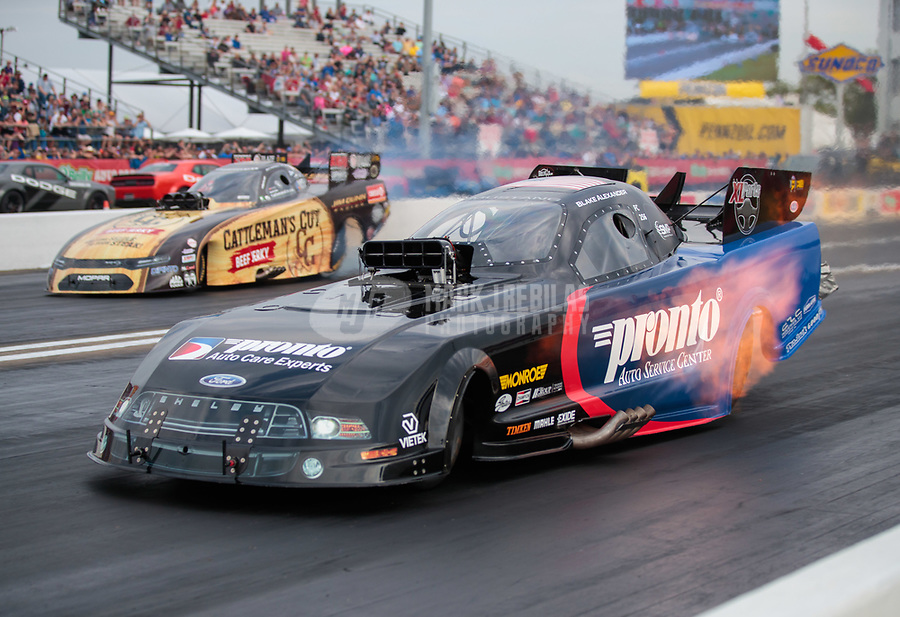 Apr 12, 2019; Baytown, TX, USA; NHRA funny car driver Blake Alexander (near) races alongside Jim Campbell during qualifying for the Springnationals at Houston Raceway Park. Mandatory Credit: Mark J. Rebilas-USA TODAY Sports