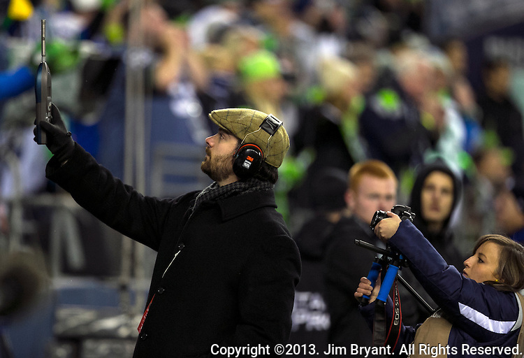 An official uses a meter to measure the decibels during the Monday night in the game against the New Orleans Saints during the second quarter at CenturyLink Field in Seattle, Washington on December 2, 2013.  The 68,338 fans that packed into CenturyLink Field set the world record for noise at an outdoor sports stadium at 137.6 decibels.<br /> The Seahawks beat the Saints 34-7 to take the best record team in the NFL. &copy;2013. Jim Bryant Photography. ALL RIGHTS RESERVED.