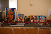 A melange of religious symbols and prayer items on the table on the 3rd floor of the Akanksha Infertility Clinic, where some surrogate mothers stay, in the small town of Anand, Gujarat, India. The Akanksha Infertility Clinic is known internationally for its surrogacy program and currently has over a hundred surrogate mothers pregnant in their environmentally controlled surrogate houses. .Photo by Suzanne Lee