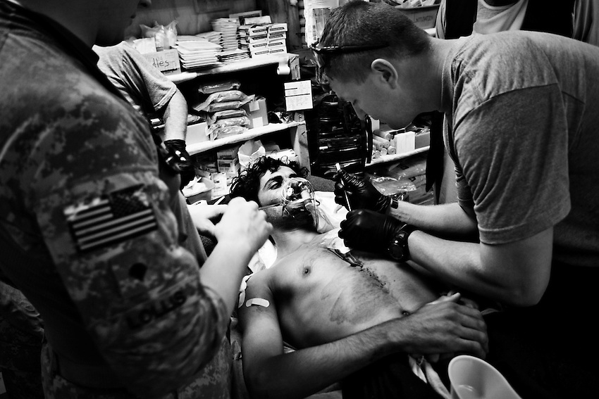 Sgt. Anthony Blake (R) and Spc. James Lollis (L) treat an Afghan construction worker wounded by a grenade in an attack by the Taliban in the Pesh Valley near the village of Kandigal, COP Michigan, Kunar Province, Afghanistan, Sunday, Sept 27, 2009. The wounded man is a member of a construction team working on the main road through the Pesh Valley.
