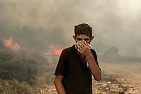 Pictured: A young man covers his face with a scarf as a fire rages in the background in Varnavas, near Kalamos.<br /> Re: A forest fire has been raging in the area of Kalamos, 20 miles east of Athens in Greece. There have been power cuts, country houses burned and children camps evacuated from the area.