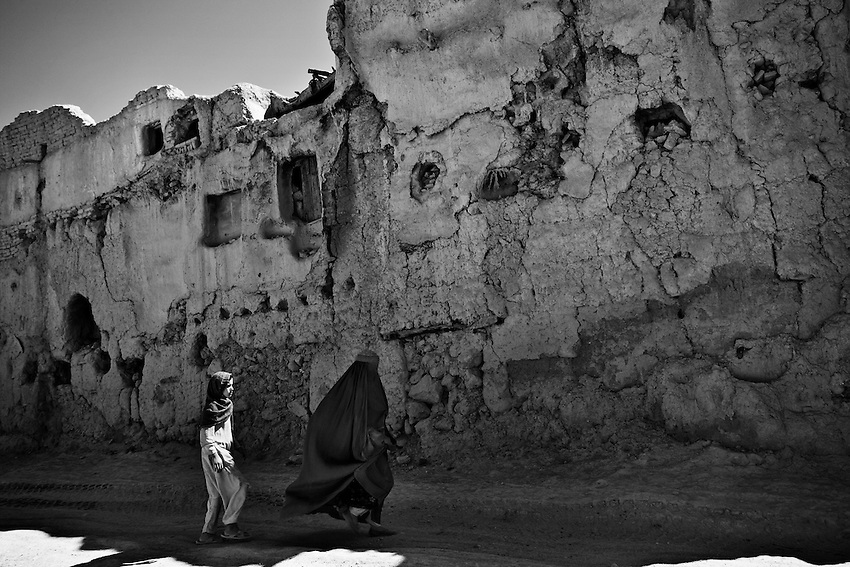 An Afghan woman and girl walk passed a damaged building in Charkh, Afghanistan, Saturday, May 16, 2009.