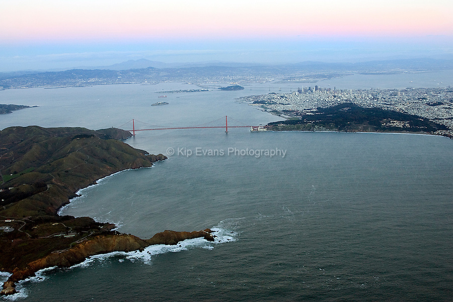 Aerial view of San Francisco Bay at sunset. Image shows the Golden Gate Bridge and a cargo ship heading out to sea.