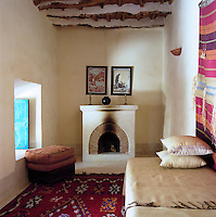 In this small whitewashed sitting room the walls, floor and furniture are decorated with locally made textiles and carpets