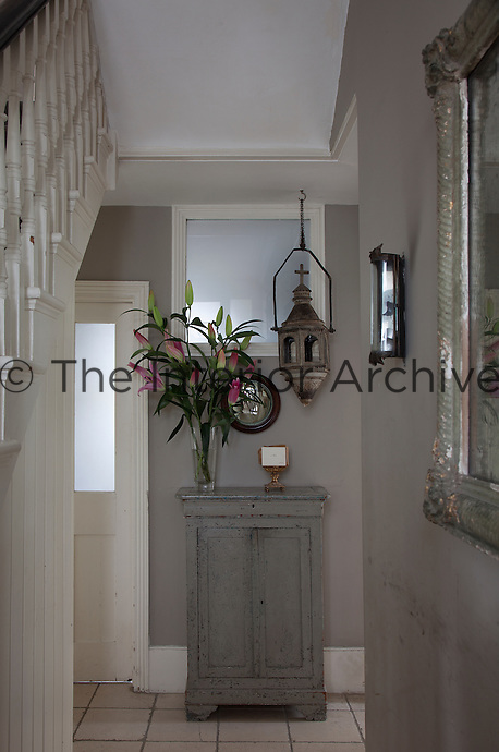 A flower arrangement of bright pink lilies enlivens the dove grey walls of the entrance hall