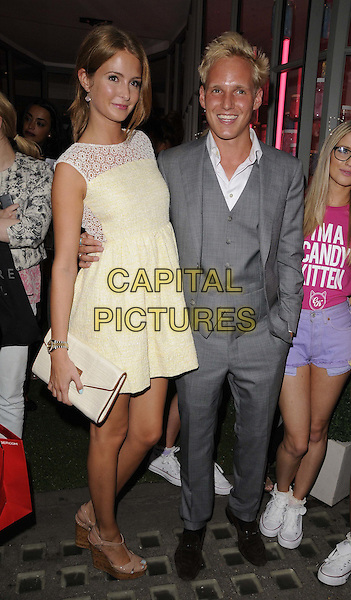 Millie Mackintosh & Jamie Laing.The Candy Kittens pop up shop launch party, Candy Kittens, London, England, August 7th, 2012.full length yellow white sleeveless lace dress clutch bag grey gray suit waistcoat arm around waist .CAP/CAN.©Can Nguyen/Capital Pictures.