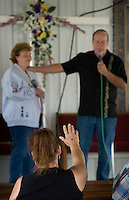 A woman raises her hand in celebration during a gospel singer's performance at the Perry County Fair in New Lexington, Ohio.<br />