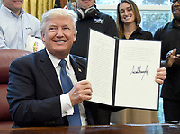 United States President Donald J. Trump displays the National Manufacturing Day Proclamation after signing it in the Oval Office of the White House in Washington, DC on Friday, October 6, 2017.<br /> CAP/MPI/CNP/RS<br /> &copy;RS/CNP/MPI/Capital Pictures